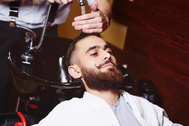 Barbeiro ou cabeleireiro lava a cabeça do cliente