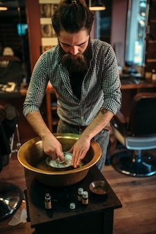 Barbeiro preparando espuma de barbear em uma tigela de cobre na barbearia.