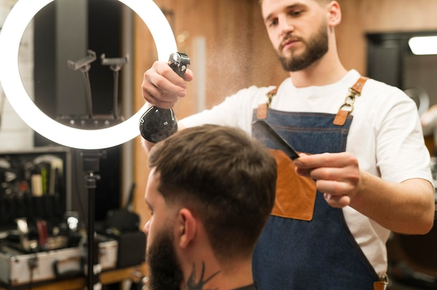 Barbeiro preparando o cabelo de um cliente para cortar