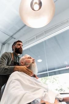 Barbeiro, preparando o cliente para aparar no salão de cabeleireiro