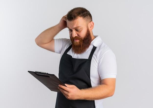 Barbeiro profissional barbudo chateado com avental segurando uma prancheta olhando para ela confuso e coçando a cabeça em pé sobre uma parede branca
