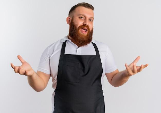 Barbeiro profissional barbudo com avental e braços abertos enquanto faz perguntas em pé sobre uma parede branca
