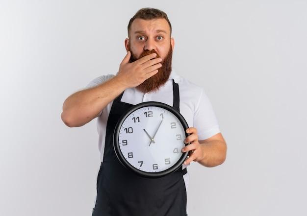Barbeiro profissional barbudo com avental mostrando o despertador parecendo surpreso cobrindo a boca com uma mão em pé sobre uma parede branca