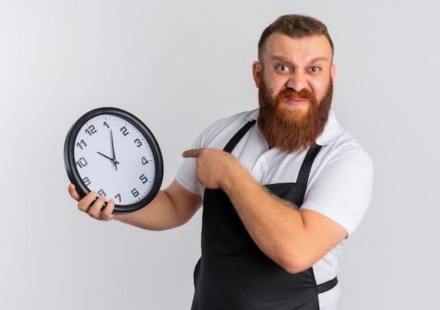 Barbeiro profissional barbudo com avental mostrando o relógio de parede apontando com o dedo para ele descontente em pé na parede branca