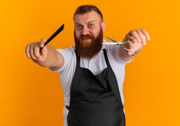 Barbeiro profissional barbudo com avental mostrando uma tesoura e uma escova de cabelo parecendo confuso em pé sobre a parede laranja
