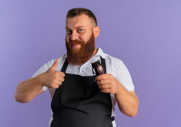 Barbeiro profissional barbudo com avental segurando uma máquina de corte de cabelo e sorrindo amigável mostrando os polegares em pé sobre a parede roxa