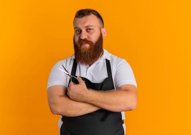 Barbeiro profissional barbudo com avental segurando uma tesoura com expressão confiante em pé sobre a parede laranja