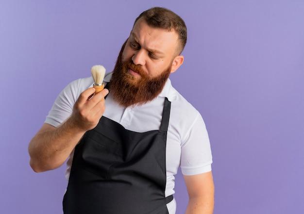 Barbeiro profissional barbudo de avental segurando um pincel de barbear olhando para ele com uma cara séria de pé sobre a parede roxa