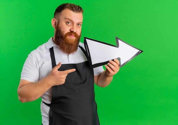 Barbeiro profissional barbudo de avental segurando uma grande seta apontando para a direita apontando com o dedo em pé sobre a parede verde