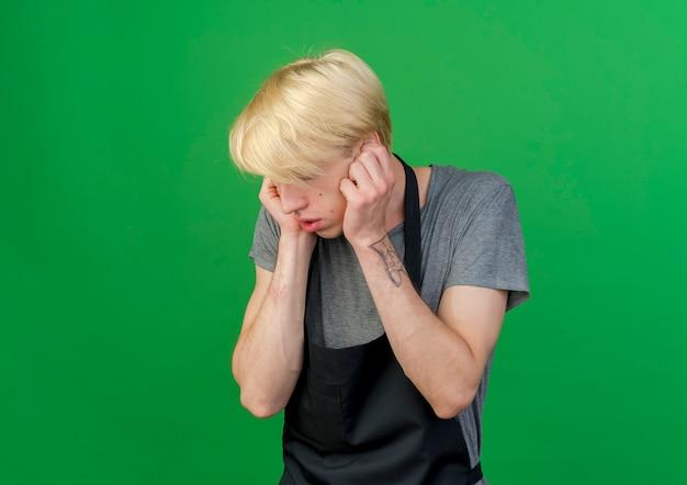 Barbeiro profissional com avental cobrindo as orelhas com os dedos