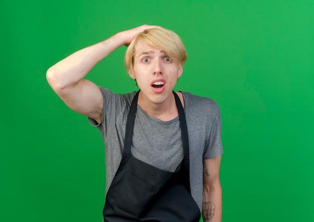 Barbeiro profissional com avental olhando para a câmera confuso e surpreso
