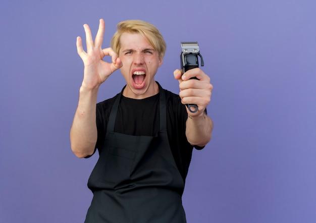 Barbeiro profissional com avental segurando o aparador louco feliz mostrando a placa de ok em pé sobre a parede azul