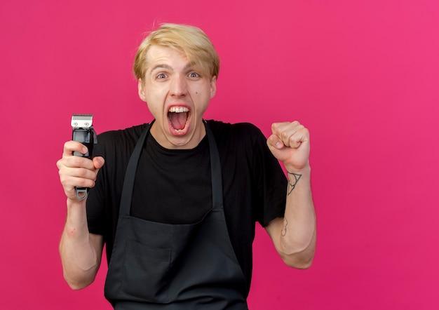 Barbeiro profissional com avental segurando o cortador de punho cerrado, gritando feliz e animado
