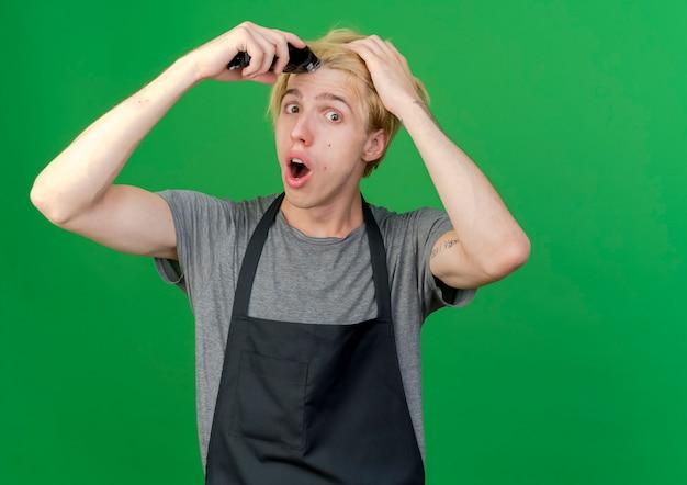 Barbeiro profissional com avental segurando um aparador tentando cortar o cabelo parecendo surpreso