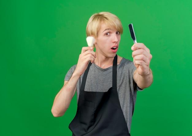 Barbeiro profissional com avental segurando uma navalha e um pincel de barbear parecendo surpreso