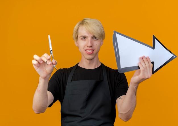Barbeiro profissional com avental segurando uma seta branca e uma tesoura, olhando para a frente, sorrindo confiante em pé sobre a parede laranja