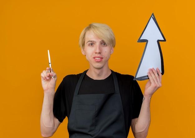 Barbeiro profissional com avental segurando uma seta branca e uma tesoura olhando para a frente sorrindo em pé sobre a parede laranja
