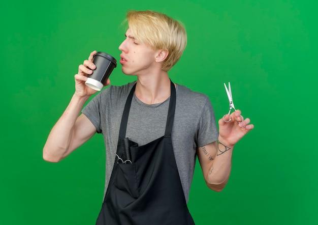 Barbeiro profissional com avental segurando uma xícara de café e uma tesoura indo beber café
