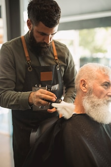 Barbeiro profissional com escova preparando o cabelo de pescoço para barbear