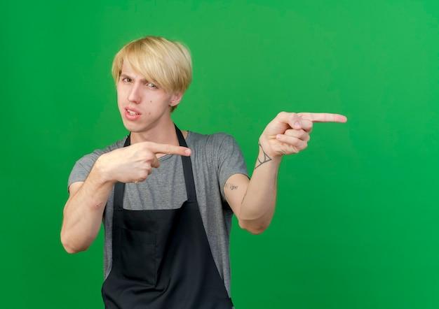 Barbeiro profissional de avental apontando para o lado com o dedo indicador e uma expressão séria