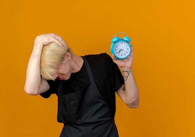 Barbeiro profissional de avental segurando um despertador, confuso e muito ansioso em pé sobre a parede laranja