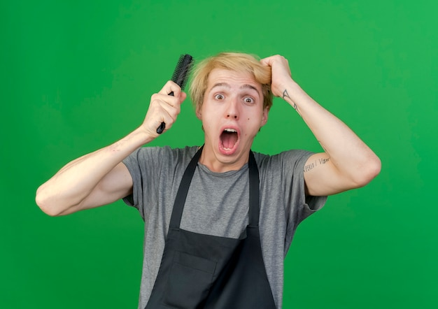 Barbeiro profissional de avental segurando uma escova de cabelo e tocando seu cabelo recebendo choque