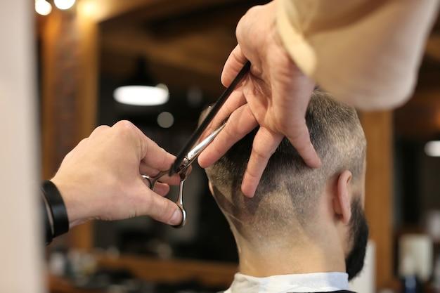 Barbeiro profissional trabalhando com cliente em salão de cabeleireiro