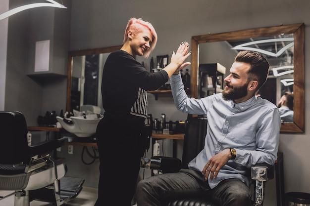 Barbeiro que dá alta cinco ao cliente