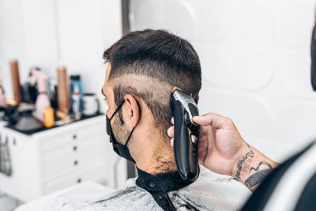 Barbeiro raspando a nuca de um homem caucasiano com uma máscara sentado em uma barbearia