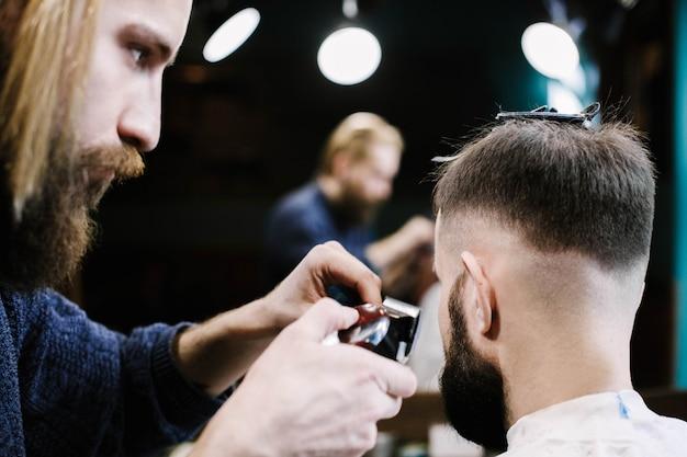 Barbeiro remove o cabelo do homem com um clipper
