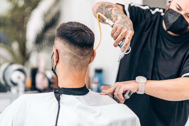 Barbeiro removendo o excesso de cabelo de um cliente sentado em uma cadeira com um soprador de ar em uma barbearia