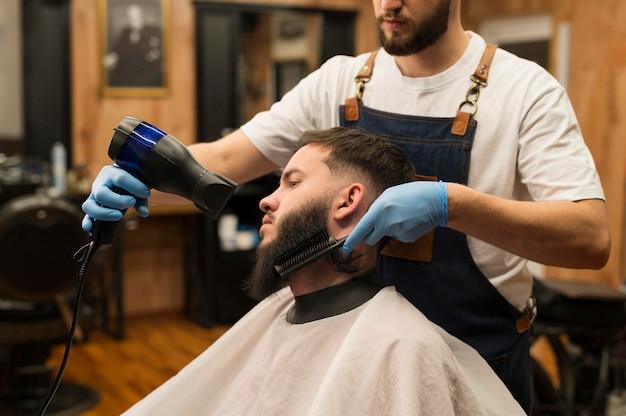 Barbeiro secando a barba de um cliente masculino