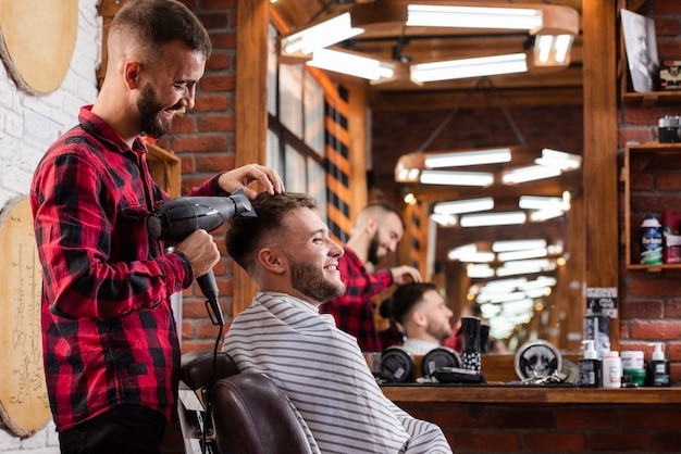 Barbeiro, secando o cabelo dos clientes enquanto sorrindo