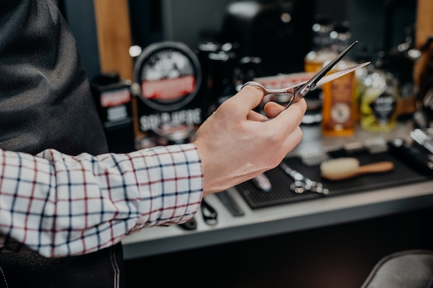 Barbeiro segurando uma tesoura na barbearia