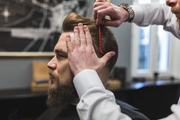 Barbeiro sem rosto, penteando o cabelo do cliente