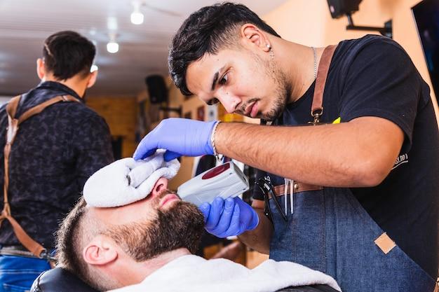 Barbeiro trabalhando em sua barbearia. conceito de bem-estar e beleza.