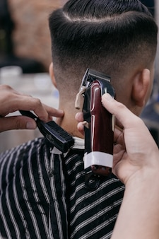 Barbeiro usando máquina de cortar cabelo e pente para cortar o cabelo na barbearia.