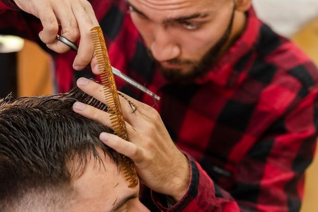 Barbeiro, usando uma tesoura e pente para cabelo