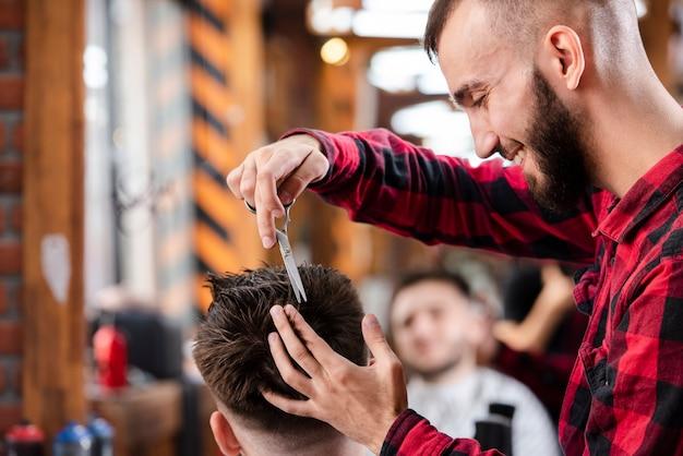 Barbeiro usando uma tesoura para fazer um penteado