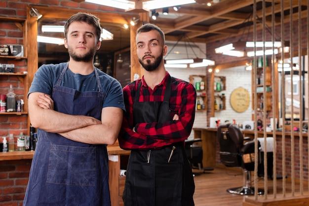 Barbeiros de tiro médio em pé com os braços cruzados