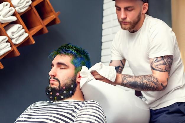 Barber enxugando a cabeça de seu cliente com uma toalha