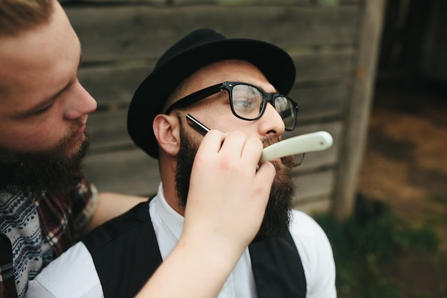 Barber faz a barba de um homem barbudo em um ambiente vintage