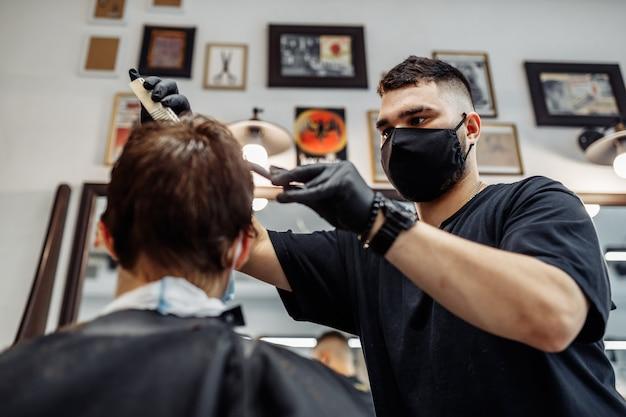 Barber faz um corte de cabelo e penteado em uma barbearia, salão de beleza. cabelo saudável.