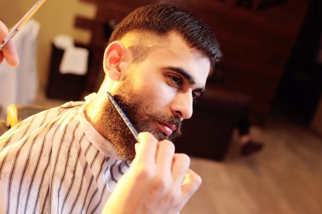 Barber faz uma barba estilosa para o cliente - um jovem bonito e com bigode. barbear a barba na barbearia