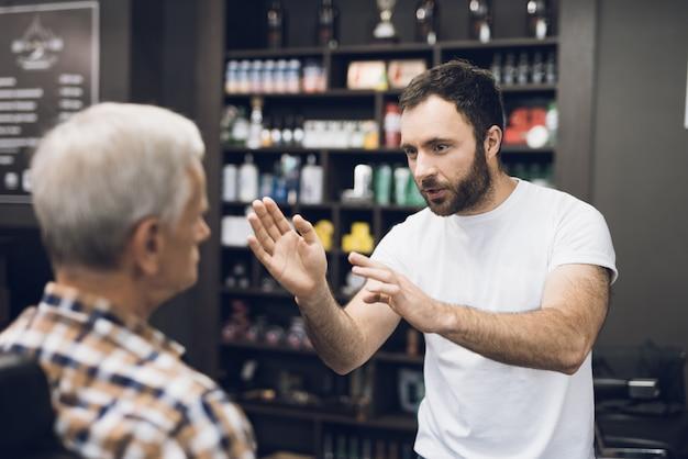 Barber talk client no estúdio de cabeleireiro.