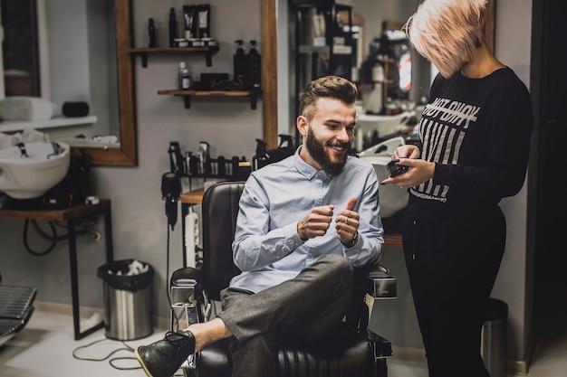 Barbero que mostra cosméticos ao cliente