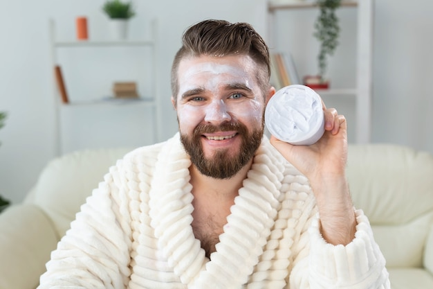 Barbudo aplicando creme anti-rugas no rosto, cuidados com a pele e spa para homem conceito