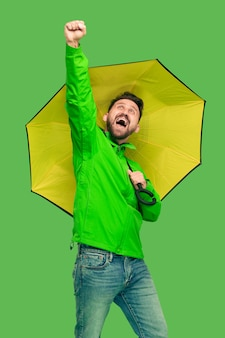 Barbudo bonito sorridente jovem feliz segurando o guarda-chuva e olhando para a câmera isolada no estúdio verde na moda vívido.