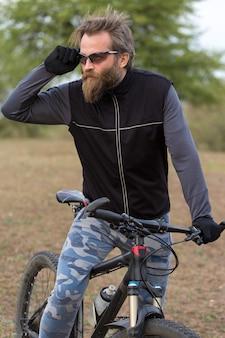 Barbudo brutal de esportes em uma bicicleta de montanha moderna. ciclista nas colinas verdes na primavera.