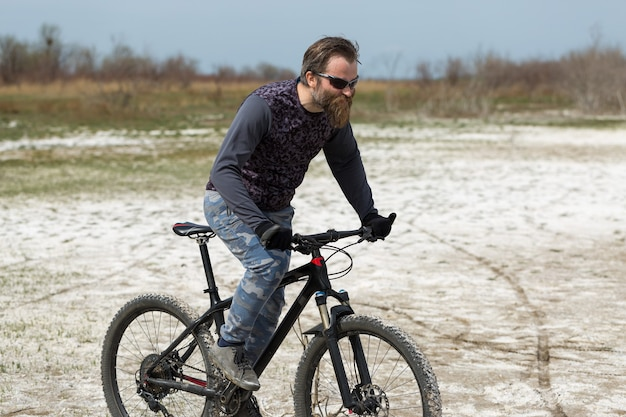 Barbudo brutal de esportes em uma bicicleta de montanha moderna. um ciclista em um lugar deserto de sal à beira do lago.